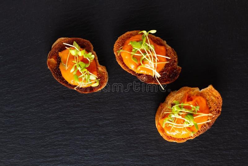 Gezonde hummus van de de veganistpompoen van het voedselconcept met vlas microgreen canapés brood op de zwarte raad van de leiste stock afbeeldingen