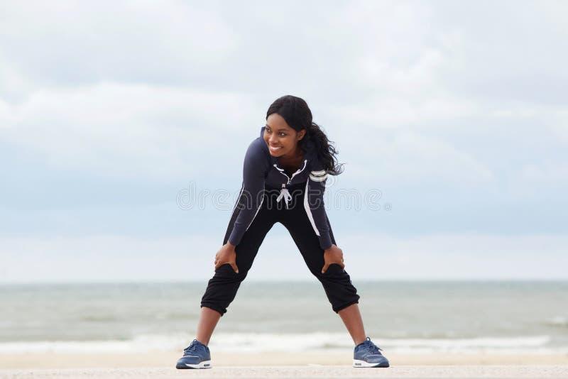 Gezonde jonge Afrikaanse Amerikaanse vrouw die met handen op knieën bij het strand rusten stock afbeeldingen