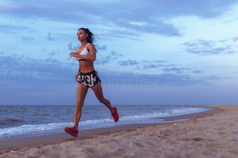 Gezonde jonge de sleepagent die van de geschiktheidsvrouw op zonsopgangkust lopen stock afbeeldingen