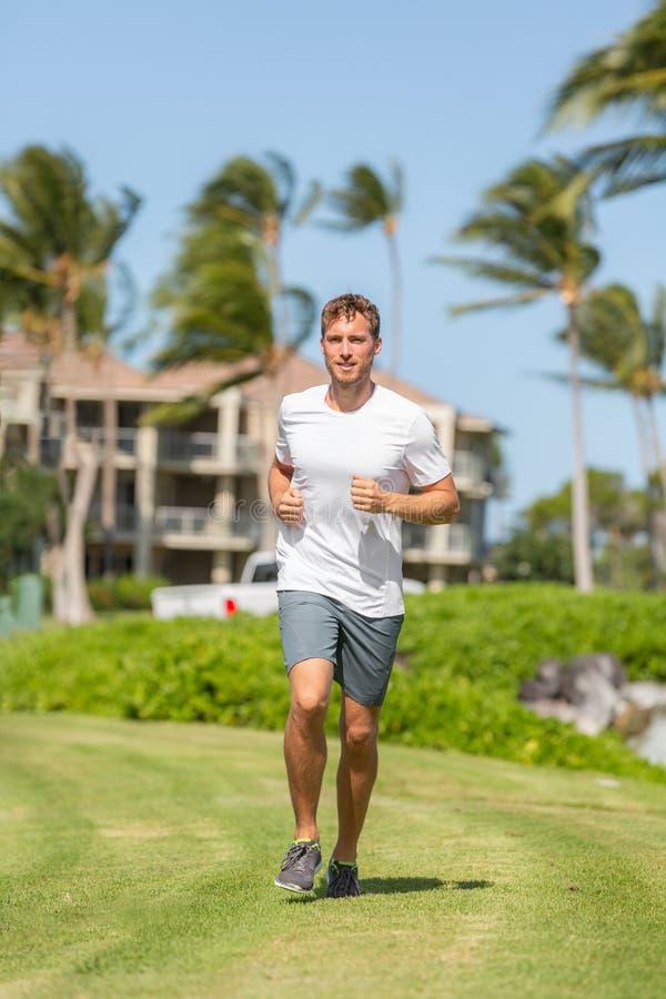 Gezonde jonge mensenagent die jogging gelukkig op de graszomer in openlucht uitwerken - actieve levensstijl stock fotografie