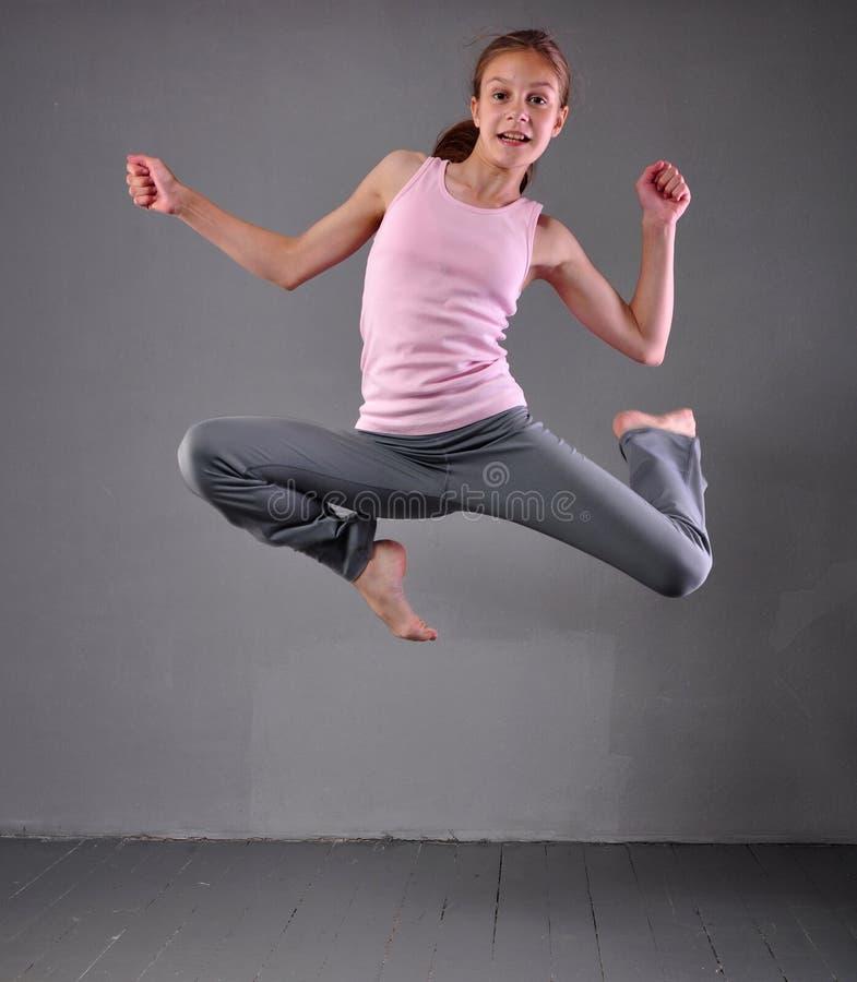 Gezonde jonge spiertiener die en in studio overslaan dansen Kind die met het springen op grijze achtergrond uitoefenen stock foto