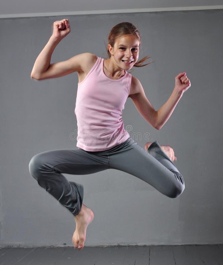 Gezonde jonge spiertiener die en in studio overslaan dansen Kind die met het springen op grijze achtergrond uitoefenen stock foto's