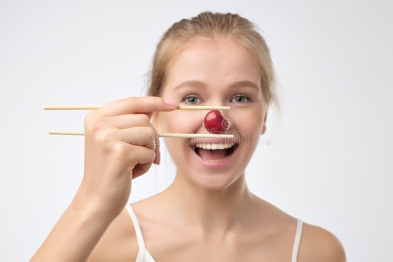 Gezonde jonge vrouw die één rode kers met stokken houden royalty-vrije stock afbeeldingen