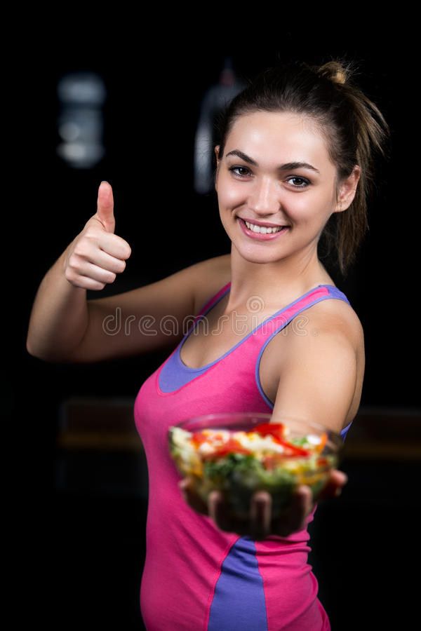 Gezonde jonge vrouw die groenten groene salade eten bij donkere gymnastiek stock foto