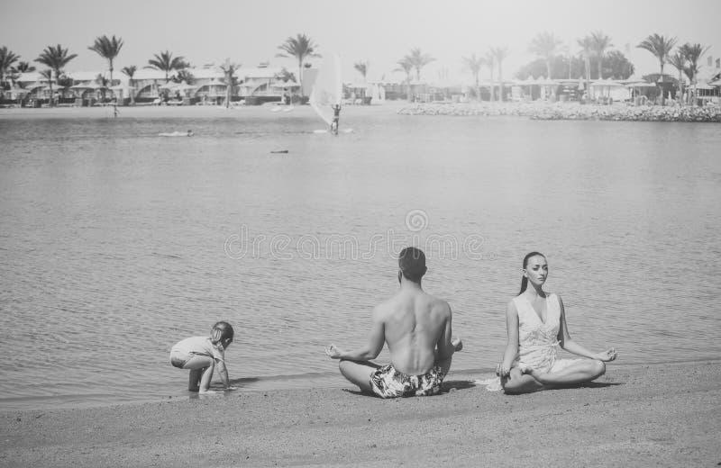 Gezonde Levensstijl de familie van gelukkige kind, mens en vrouw die, yoga stelt de mediteren stock foto