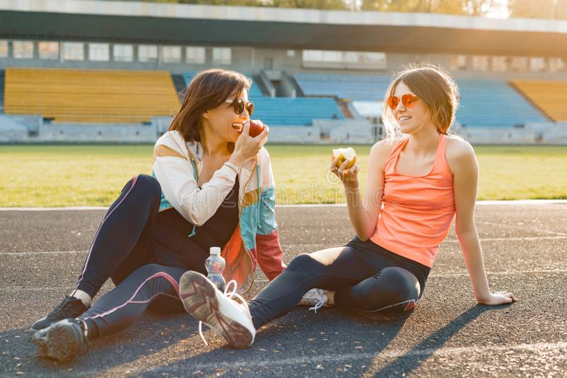 Gezonde levensstijl en gezond voedselconcept Glimlachende geschiktheidsmoeder en tienerdochter die samen appelzitting op stadion  stock foto