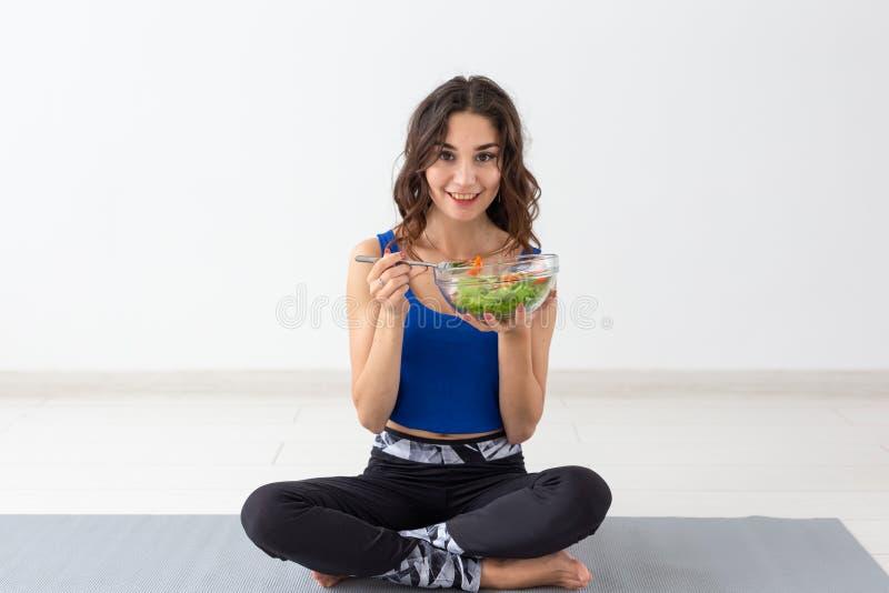 Gezonde levensstijl, mensen en sportconcept - Yogavrouw met een kom plantaardige salade royalty-vrije stock foto