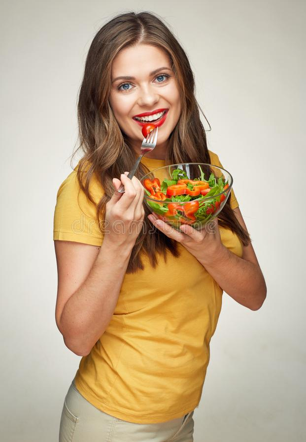 Gezonde levensstijl met glimlachende vrouw die vegetarische salade eten stock fotografie