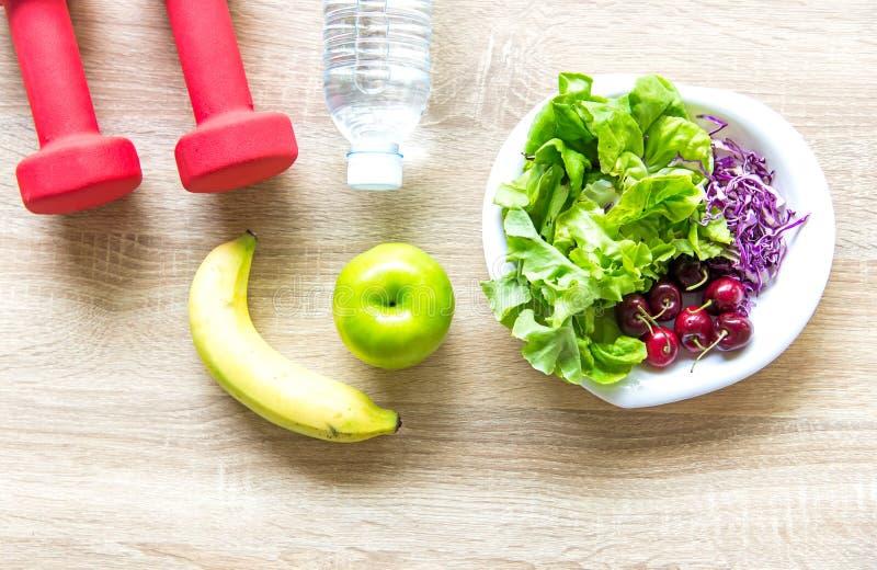 Gezonde levensstijl voor vrouwendieet met sportmateriaal, tennisschoenen, die band, fruit gezonde groene appelen en fles water me stock afbeeldingen