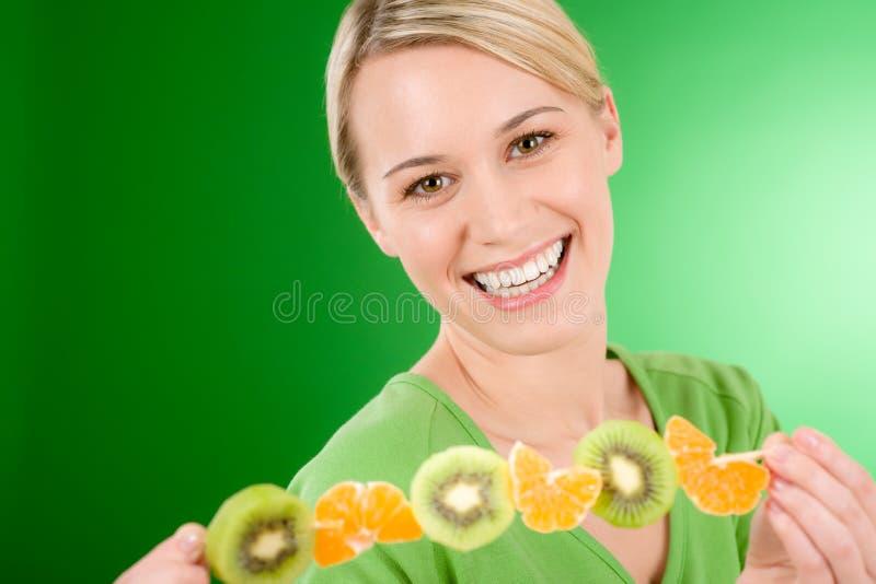 Gezonde levensstijl - vrouw die kiwi en sinaasappel eet royalty-vrije stock foto