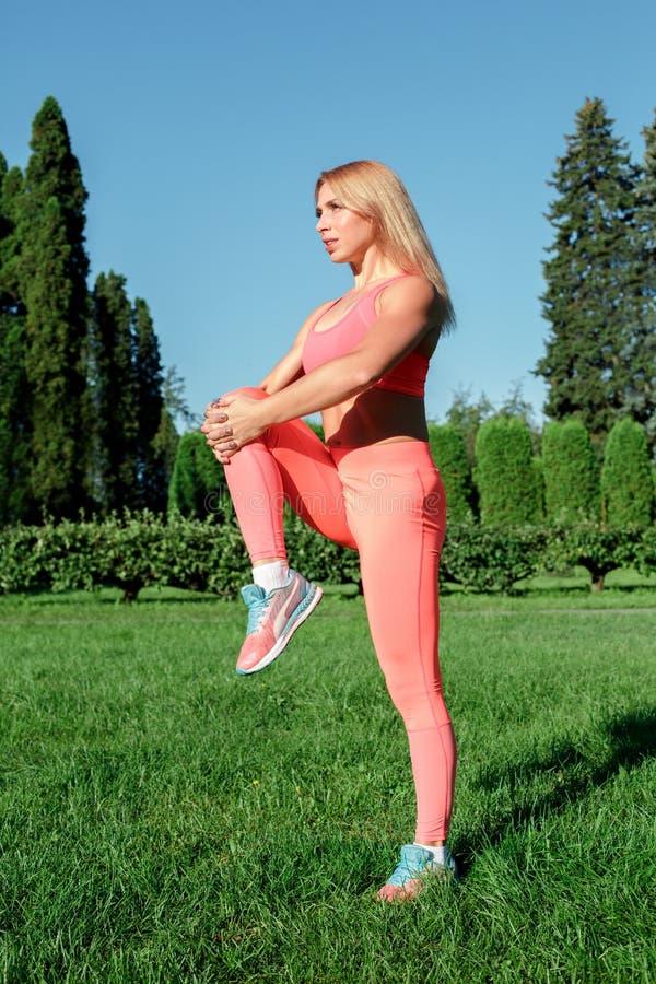 Gezonde Levensstijl Vrouw het praktizeren de yoga die zich in openlucht holdingsbeen bevinden concentreerde omhoog volledig licha stock fotografie
