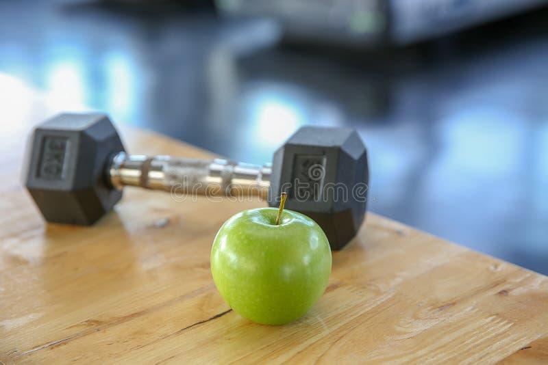 Gezonde levensstijlsport Dumbells, en gezond voedsel op houten stock afbeeldingen