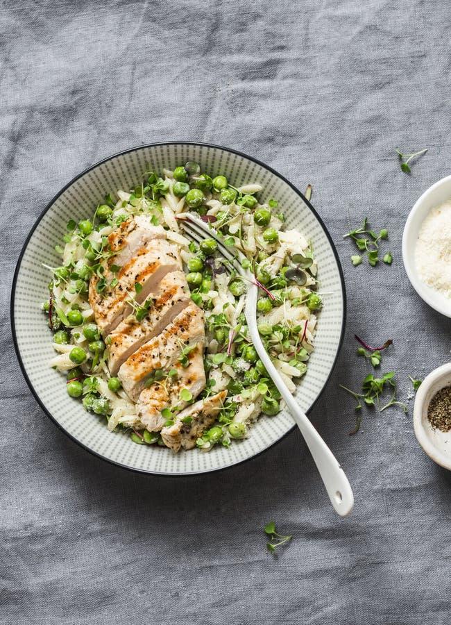 Gezonde lunch - orzo, groene erwten, risotto van de lentekruiden en geroosterde kippenborst op een grijze achtergrond stock foto