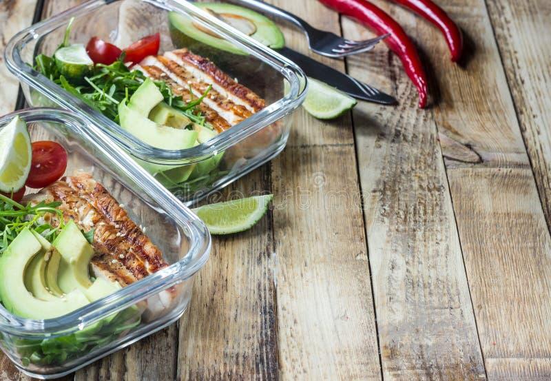 Gezonde maaltijd prep containers met rukola, de grill van Turkije, tomaten en avocado stock foto