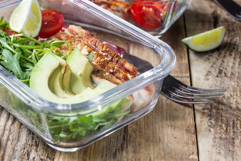Gezonde maaltijd prep containers met rukola, de grill van Turkije, tomaten en avocado stock afbeeldingen