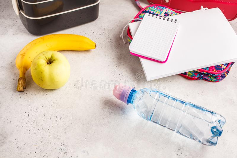 Gezonde maaltijd prep containers, notitieboekje en rugzak, vruchten en stock afbeelding