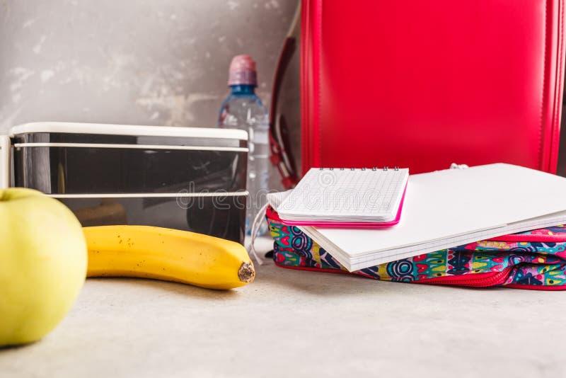 Gezonde maaltijd prep containers, notitieboekje en rugzak, vruchten en royalty-vrije stock afbeelding