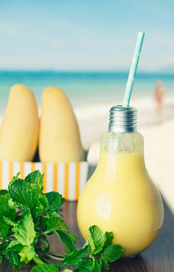 Gezonde mango smoothie in gloeilampenglas met vruchten en munt stock foto