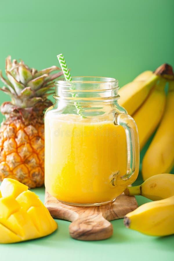 Gezonde mangoananas smoothie in metselaarkruiken stock fotografie