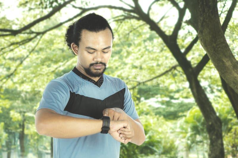 Gezonde mens die smartwatch op park bekijken stock afbeeldingen