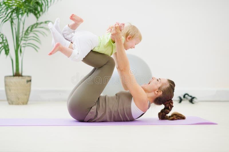 Gezonde moeder en baby die gymnastiek maken stock afbeeldingen