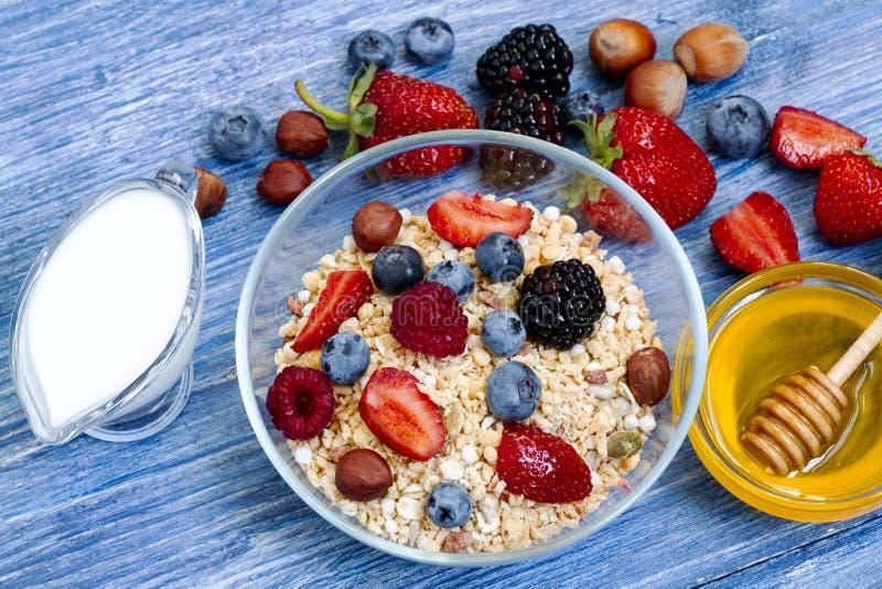 Gezonde muesli met framboos, bosbes, aardbei, Blackberry, hazelnoot, melk en honing op blauwe houten rustieke lijst royalty-vrije stock foto