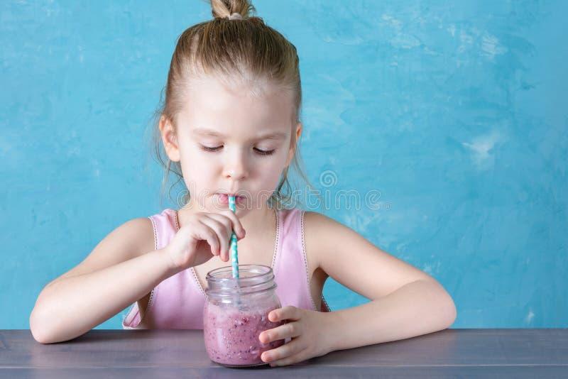 Gezonde natuurlijke drank, gezond voedsel Het kind drinkt bessen smoothie door een stro stock afbeelding