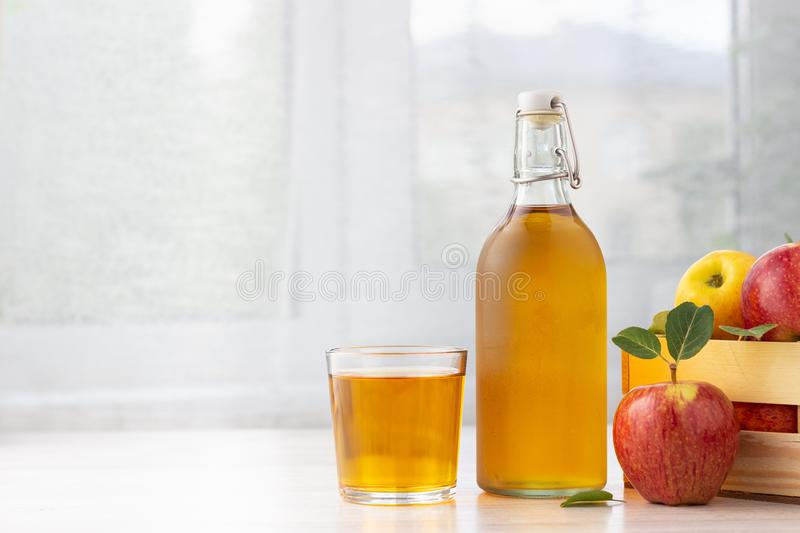 Gezonde natuurvoeding Apple-ciderazijn of sap in glasfles en verse rode appelen stock fotografie