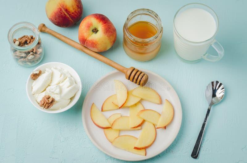 Gezonde ontbijtachtergrond Perzik, honing, melk, kwark en okkernoot op een blauwe lijst Hoogste mening stock afbeelding