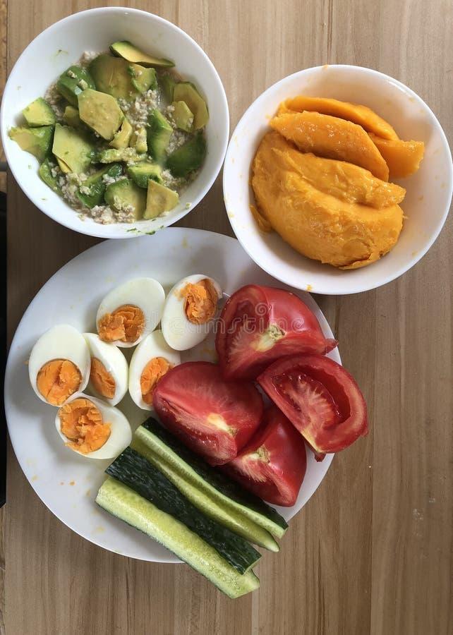 Gezonde ontbijteieren, groenten, mango en avocado stock afbeeldingen