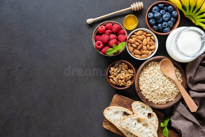Gezonde ontbijtingrediënten op zwarte concrete achtergrond stock afbeeldingen