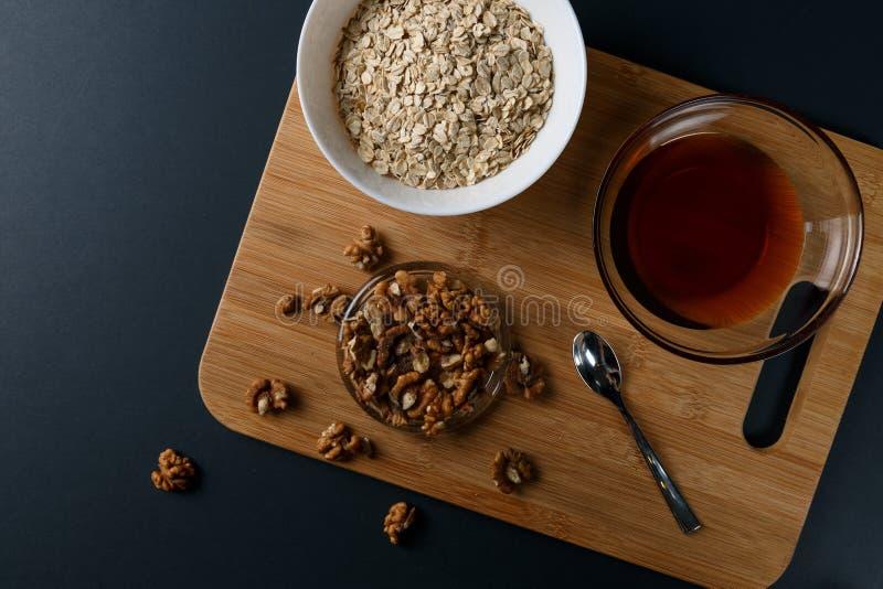 Gezonde Ontbijtingredi?nten: honing, okkernoten, havermeel op een donkere achtergrond stock fotografie