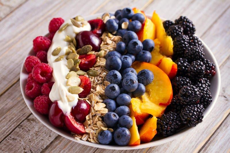 Gezonde ontbijtkom - bessen, muesli, vruchten, yoghurt en zonnebloemzaden De gezonde maaltijd van de detoxochtend royalty-vrije stock afbeelding