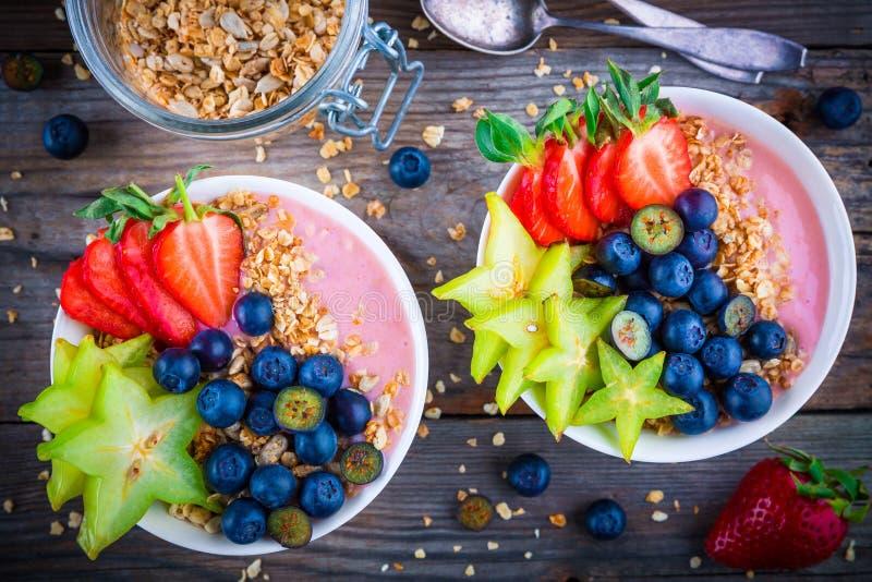 Gezonde ontbijtkom: framboos smoothies met granola, bosbessen, aardbeien en carambola stock foto