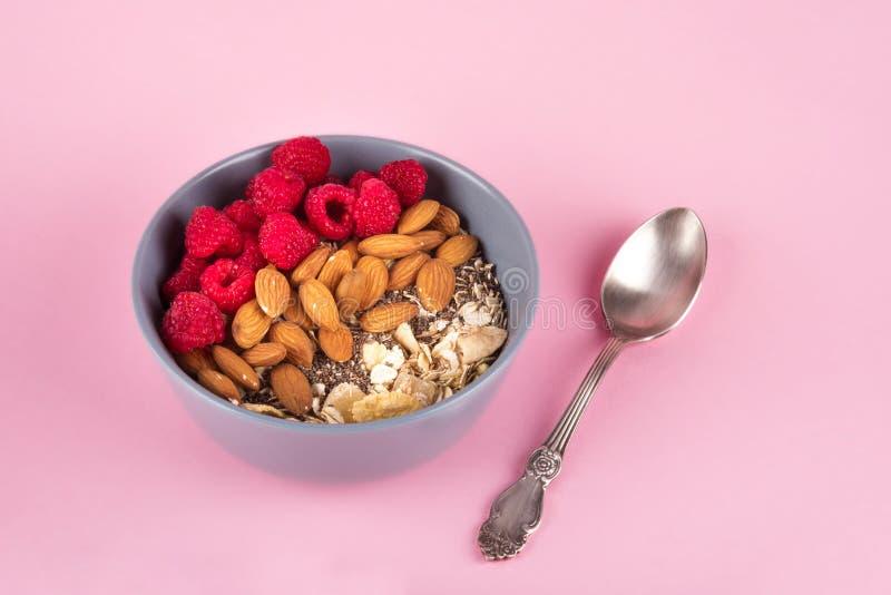 Gezonde ontbijtkom: havermeel met framboos, amandel, en chiazaden Rustieke lepel Roze pastelkleurachtergrond stock foto