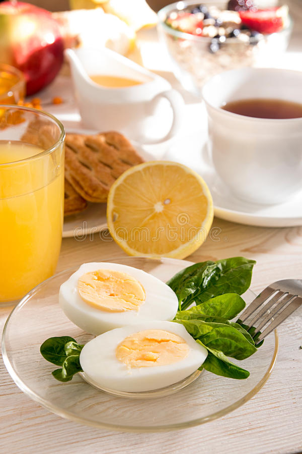 Gezonde organische ontbijt Gekookte eieren, kop thee, jus d'orange stock foto