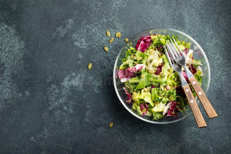 Gezonde plantaardige salade van verse tomaat, komkommer, ui, spinazie, sla en pompoenzaden in kom Dieetmenu Hoogste mening met co royalty-vrije stock foto