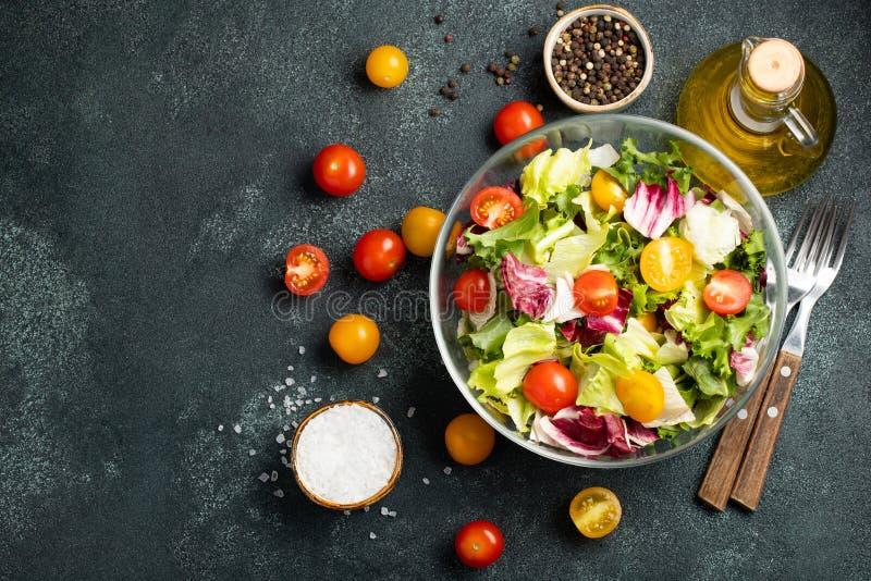 Gezonde plantaardige salade van verse tomaat, komkommer, ui, spinazie, sla en pompoenzaden in kom Dieetmenu Hoogste mening met co stock foto's