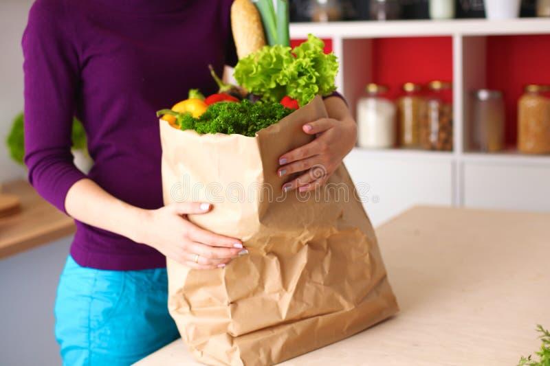 Gezonde positieve gelukkige vrouw die een document het winkelen zakhoogtepunt van fruit en groenten houden royalty-vrije stock foto