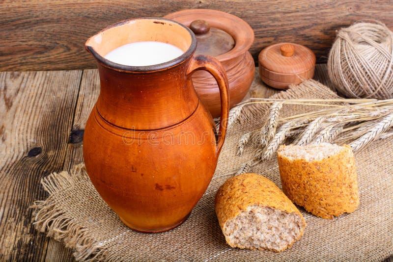 Gezonde rustieke ontbijtmelk in kruik en brood op houten lijst stock afbeeldingen