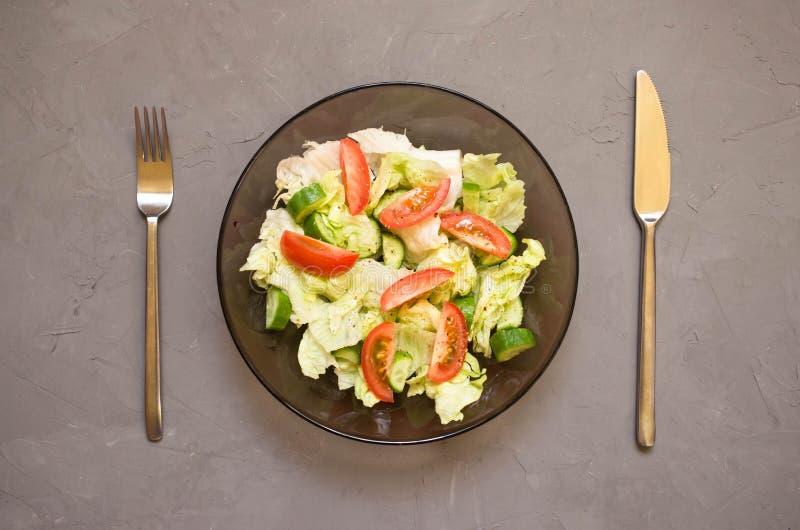 gezonde salade, groente, tomaten, komkommers, ijsberg, Bestek, grijze achtergrond Hoogste mening De ruimte van het exemplaar royalty-vrije stock foto's