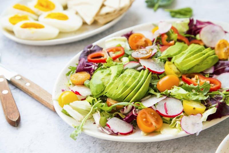 Gezonde salade met verse groenten, avocado, tomaten, peper, radijzen, groene arugula, ui, spinazie en sla met olijfolie stock afbeelding