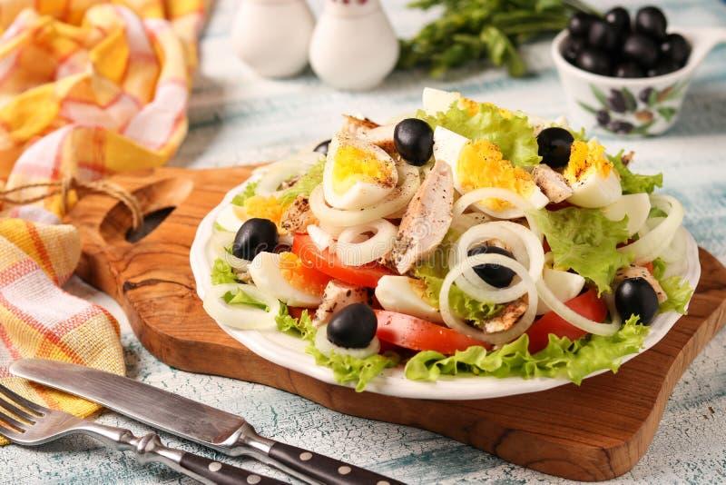 Gezonde salade van organische sla met kip, tomaten, eieren, zwarte olijven en witte uien stock foto