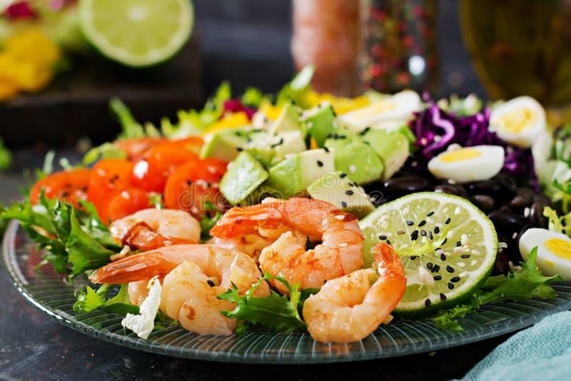 Gezonde Saladeplaat Vers zeevruchtenrecept Geroosterde garnalen en verse groentesalade - avocado, tomaat, zwarte bonen, rode kool stock foto