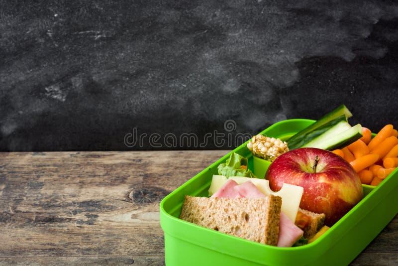 Gezonde schoolmaaltijddoos: Sandwich, groenten en fruit op houten lijst stock foto