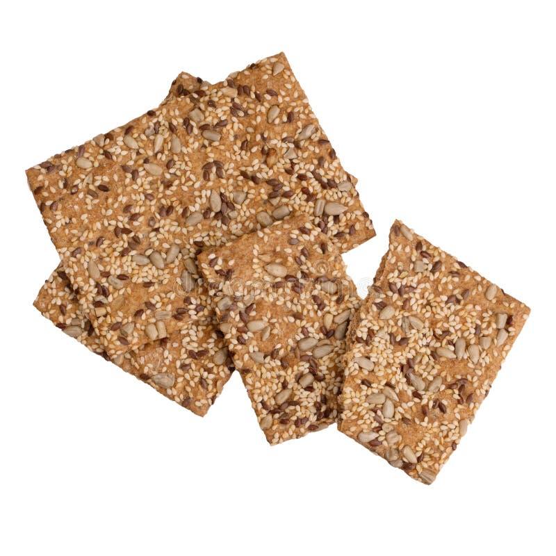 Gezonde snack, volkorenmeel, wholewheat crackers met zonnebloem, lijnzaad en sesamzaden Ge?soleerdj op witte achtergrond stock fotografie