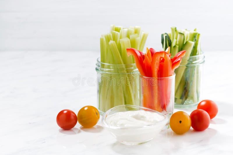 gezonde snacks, gemengde groenten en yoghurt op een witte lijst stock afbeelding