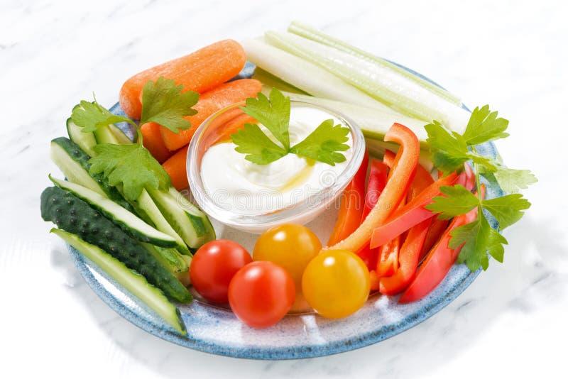 Gezonde snacks, gemengde verse groenten en yoghurt op een plaat stock afbeelding