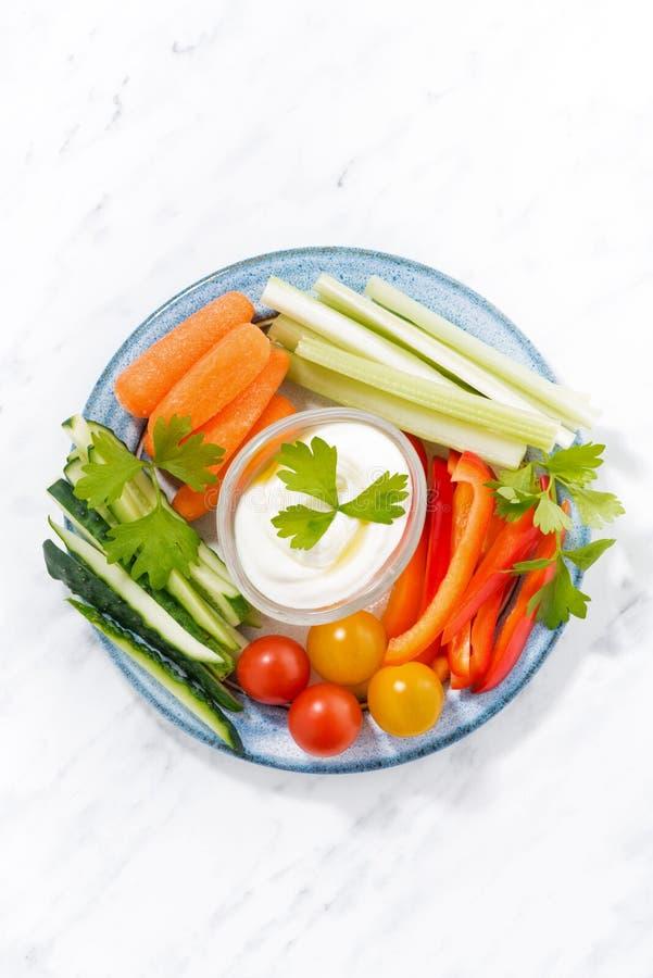Gezonde snacks, gemengde verse groenten en yoghurt op een plaat stock foto