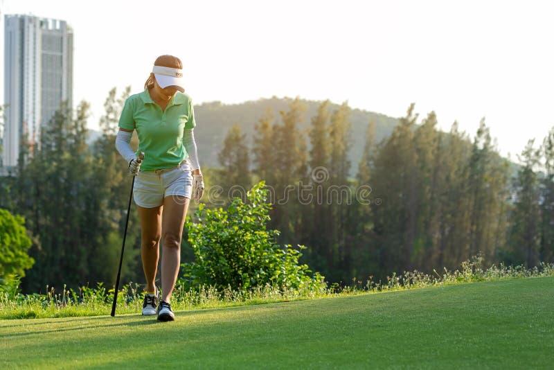 Gezonde sport Golfspeler het Aziatische sportieve vrouw ontspant lopen op fairway voor de gezette golfbal op de groene tijd van d stock foto's